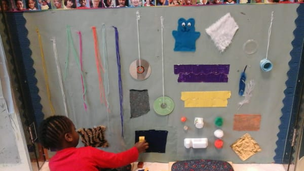 Exploring the sensory wall at Marys Pre-School